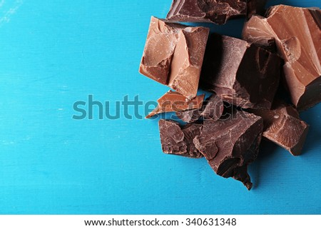Dark and milk chocolate pieces on color wooden background - stock photo