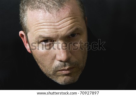 Dark and moody portrait of serious looking male adult - stock photo