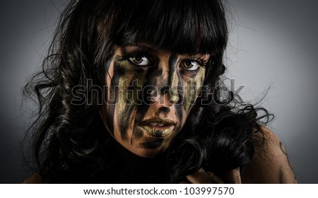 Dark and mysterious a pretty girl stands in shadow with camoflauge paint on her face - stock photo