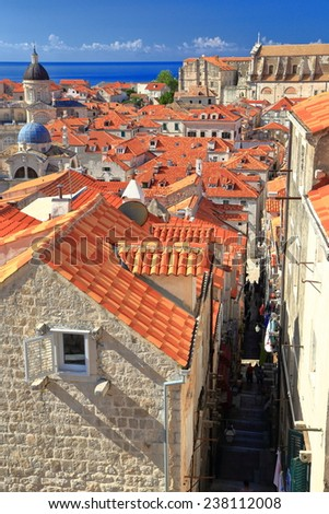 Dark and narrow street and orange rooftops in the old town of Dubrovnik, Croatia - stock photo