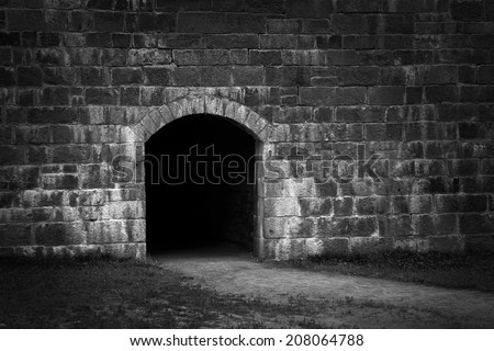 Dark and scary passage way in old stone wall, in black and white - stock photo