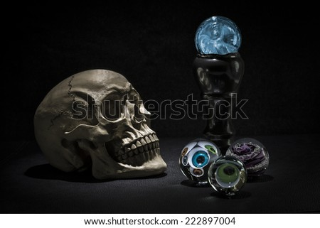 Dark and shadowy human skull in a pool of light. Crystal balls with eyeballs looking out