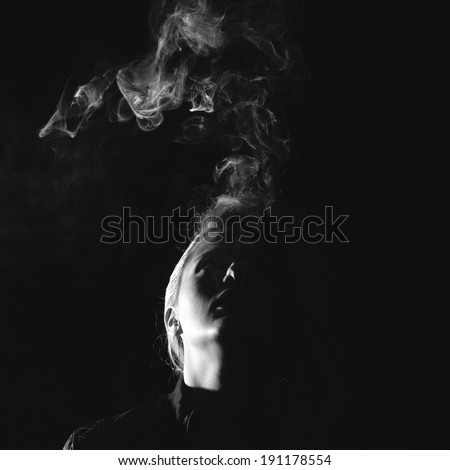 dark and sullen shot of a young woman smoking over a black background - stock photo