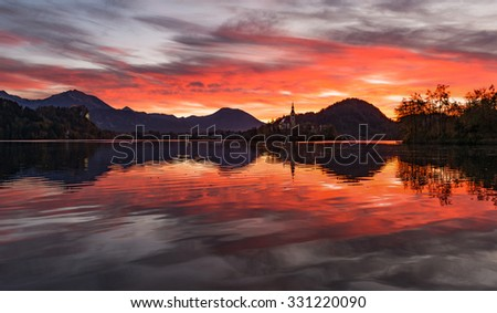 Dark and vivid red sunrise at lake Bled in Slovenia. - stock photo