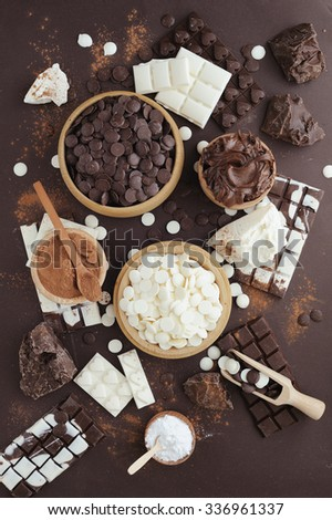 Dark and white chocolate chips, bar, sugar powder, cacao and chocolat butter on brown background