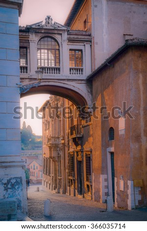 Dark artistic old historic reinassance arches and palace at dawn, lit by golden sunlight reflecting on red facades in Rome, Italy - stock photo