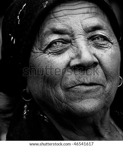 Dark artistic portrait of expressive senior lady - stock photo