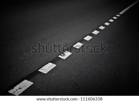 Dark asphalt road background with marking lines. Close up photo - stock photo