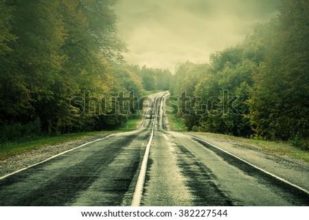 Dark asphalt road under a storm sky. - stock photo