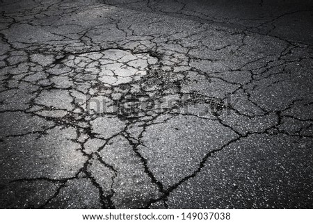 Dark asphalt road with cracks. Background texture - stock photo