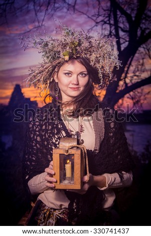 Dark beautiful woman in a mysterious stone village with lamp in her hand in sunset. Fantasy and halloween concept