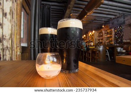 Dark beer and candle in pub setting - stock photo