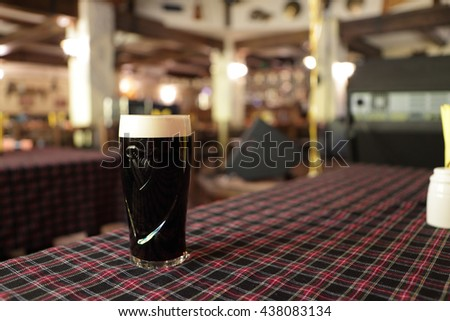 Dark beer mug on a table in Irish pub - stock photo