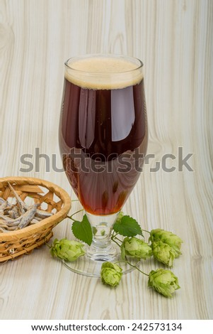 Dark Beer with hop and anchovi on the wood background - stock photo