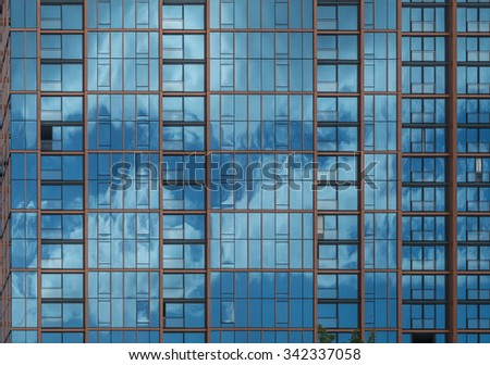 Dark blue and cloudy sky reflected in a glass building, for use as an advertising backdrop/message. - stock photo