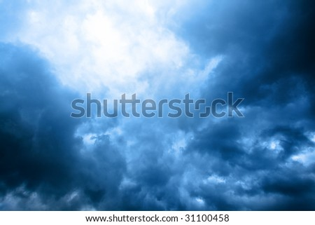 dark blue cloudly sky with ray of sunlight after storm - stock photo