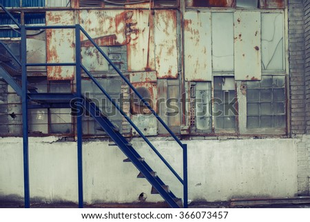 Dark blue metal stairs. Cold white industrial building wall. Vintage effect.