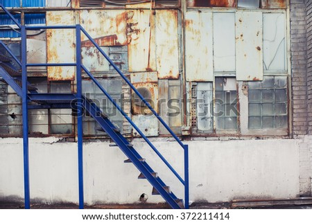 Dark blue metal stairs ladder. Cold white industrial building wall. Vintage effect.