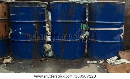 Dark blue oil barrels among industrial construction junkyard.  - stock photo