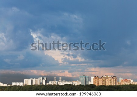 dark blue rainy clouds in pink sunset sky over city in summer evening
