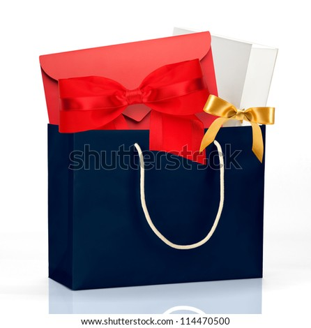 Dark blue shopping bag with gifts on white - stock photo