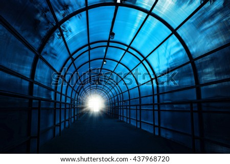 Dark blue sinister tunnel with shadows on the walls and the light at the end of it - stock photo