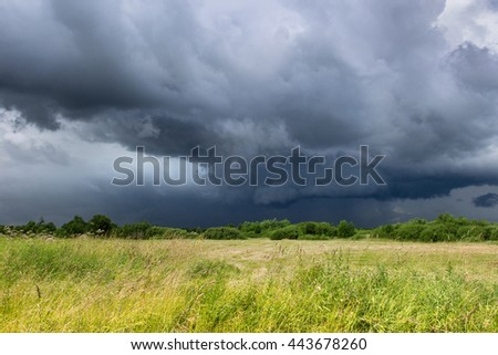 Dark blue sky and green field before thunderstorm