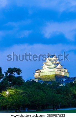 Dark blue sky behind illuminated Himeji-jo, one of 12 remaining original castles, above a park at dusk in Himeji, Japan after 2015 renovations finished. Vertical copy space