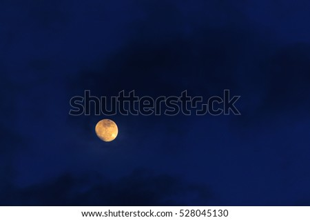 Dark blue sky with full moon and storm clouds