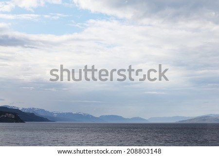 Dark blue stormy clouds over the coastal rocks, Norway - stock photo