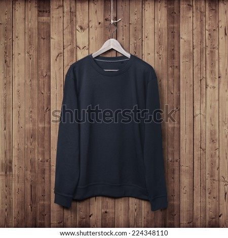 Dark blue sweater on a wood wall - stock photo