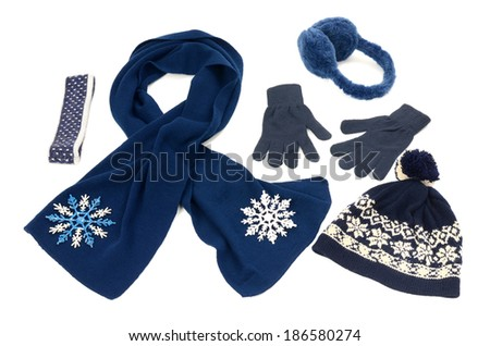 Dark blue winter accessories isolated. Wool scarf, a pair of gloves, earmuffs,a hat and a headband nicely arranged on white background.  - stock photo