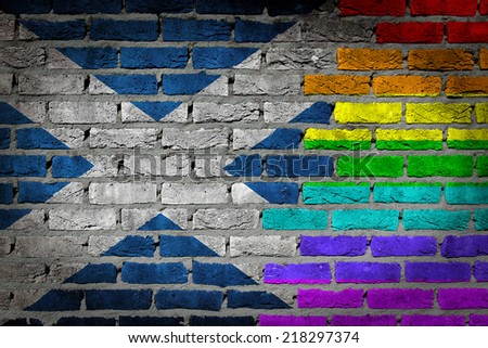 Dark brick wall texture - country flag and rainbow flag painted on wall - Scotland - stock photo