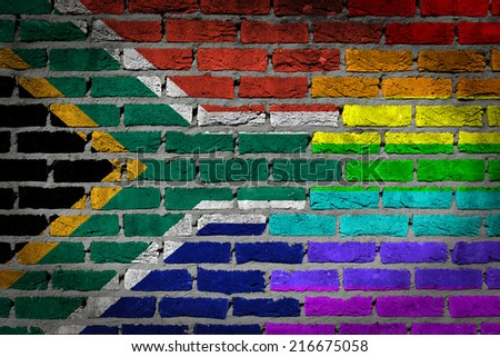 Dark brick wall texture - coutry flag and rainbow flag painted on wall - - stock photo