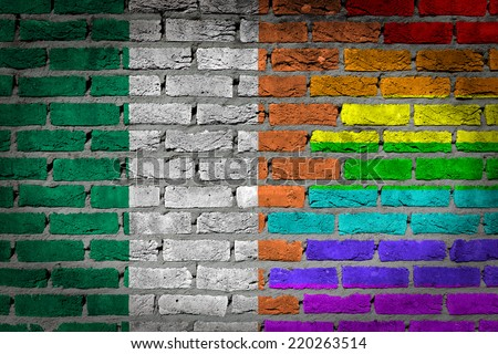 Dark brick wall texture - coutry flag and rainbow flag painted on wall - Ireland - stock photo