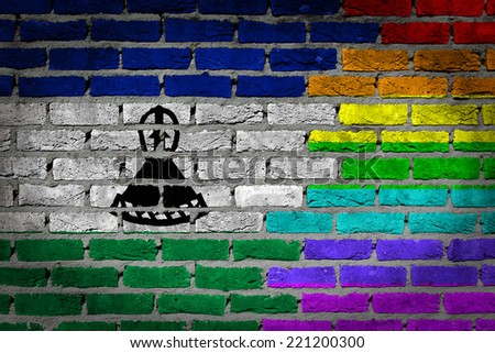 Dark brick wall texture - coutry flag and rainbow flag painted on wall - Lesotho - stock photo
