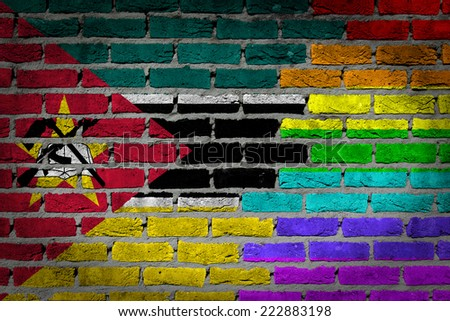 Dark brick wall texture - coutry flag and rainbow flag painted on wall - Mozambique - stock photo