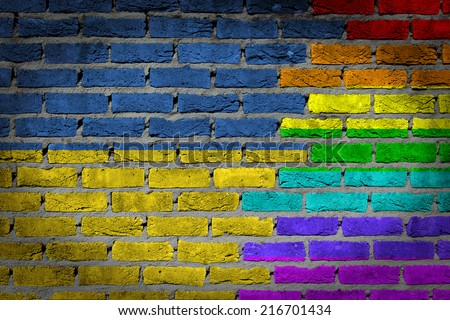 Dark brick wall texture - coutry flag and rainbow flag painted on wall - Ukraine - stock photo