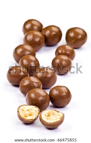 Dark brown chocolate balls and half with crisp filling over white background - stock photo