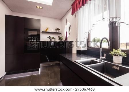 Dark brown cupboards in modern luxury kitchen - stock photo
