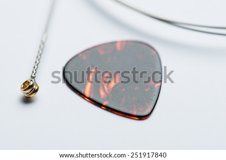 Dark brown electric guitar mediator with string on a white surface - stock photo