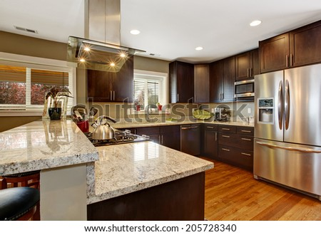 Dark brown kitchen room with steel appliances and hardwood floor - stock photo