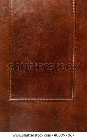 Dark brown leather texture with seam.