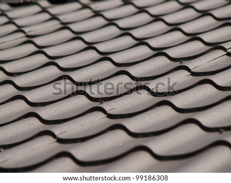 Dark brown roof. Tile. Light and shade - stock photo