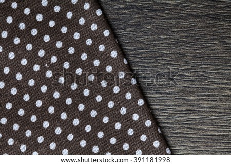Dark brown textile, napkin, tablecloth on black wooden kitchen table. View from above, top with copy space. Traditional pattern and color. - stock photo