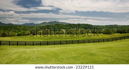 Dark brown wooden fence running through a green field on a Virginia ranch with forest and mountains in the background. - stock photo