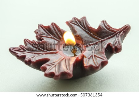 dark burgundy burning candle in the shape of a leaf against a light background