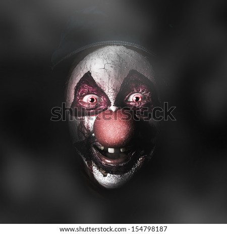 Dark carnival portrait on the face of an evil clown with a scary joker smile laughing in the black darkness. The Bogyman