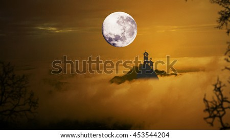 Dark castle with dramatic sky,fog, tree, full moon and cloudsover mountain, Warm orange tone. - stock photo