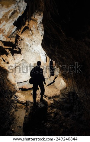 dark cave with explorer silhouette - stock photo